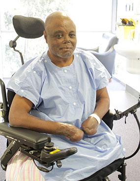 Edwin Ocha Ikwu, a smiling man in a wheelchair.