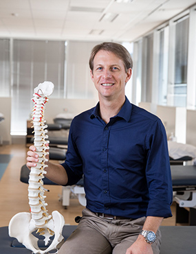 Professor Mark Hancock, with an anatomical model of a spinal column.